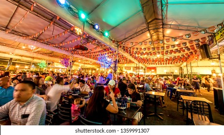 MANILA, PHILIPPINES - CIRCA MARCH 2018: View on people as they enjoy their food and drinks at the table inside of a crowded food court in Makati circa March, 2018 in Manila, Philippines.