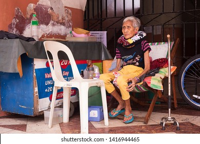 Manila, Philippines - December 21, 2016: Homeless elderly woman alone on the street