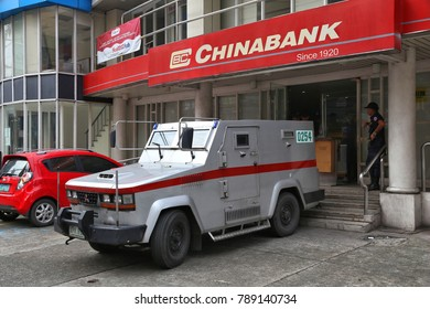 MANILA, PHILIPPINES - DECEMBER 8, 2017: Armored truck team handles money at Chinabank in Manila, Philippines. Chinabank groupa has 450 branches in Philippines.