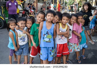 Manila, Philippines - Jan 2019: Local kids from the slums pose happily for the camera. Happiness amid poor conditions.