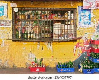 Manila, Philippines - January 17, 2017: Grilled window of a crowded neighborhood sari-sari store with trash and empty soft drink bottles and cages