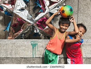Manila, Philippines - January 17, 2017: Two young boys holding a football laughing and posing in front of a wall and a broken christmas decoration
