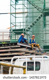 Manila, Philippines - May 30, 2019: hard working builders are resting on topped of compiled metal materials