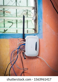 Manila, Philippines - Nov. 12 2019: A wireless home router with full Ethernet ports occupied by Ethernet cables mounted besides a typical window to share WiFi with the neighbor.