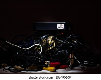 Manila, Philippines - Nov. 13 2019: ABS CBN TV Plus, a Philippines brand of set top digital TV box. Digital TV Receiver box at the top of a cluttered household cords and cables hill.