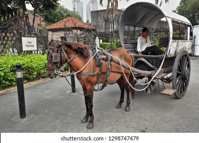 Manila, Philippines-October 24, 2016: Horse drawn kalesa-calash stops at Sta.Clara Street beside the Fort Santiago citadel while waiting for passengers visiting the Intramuros-Walled Inner City area.
