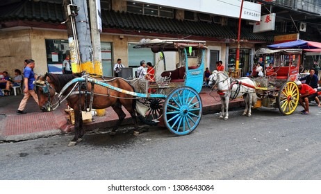Manila, Philippines-October 24, 2016: Horse drawn kalesas-calashes stop at Ongpin just pass the North Bridge over the San Lazaro Estero while waiting for passengers visiting the Binondo Chinatown area