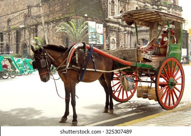 MANILA, PH-OCT. 2:Kalesa parked outside the church on October 2, 2015 in Binondo, Manila. A kalesa (also caritela/karitela) is a horse drawn calash used in the Philippines.They are rarely used today.