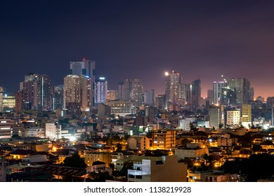 Manila skyline at night with high rise buildings and ordinary residential housing