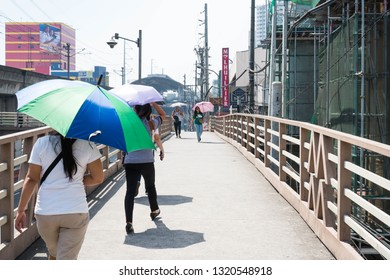 Manila/Philippines - February 7, 2019: people crossing the food bridge in a hot sunny day