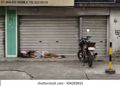 MANILA,PHILIPPINES-OCTOBER 04,2016: Beggar sleeps on a cardboard at the foot of a place in the streets of Manila on October 04, Manila,Philippines.