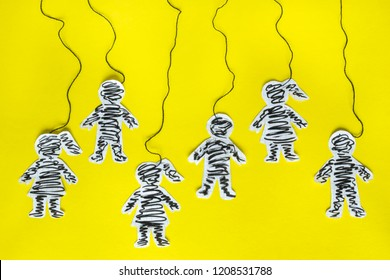 Manipulation concept, paper people with threads on the yellow background.