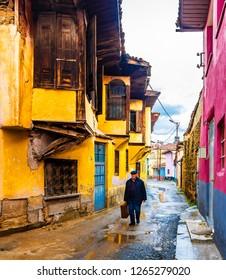 Manisa, Turkey - February 28, 2018 : Old man is traveling on Wooden based Ottoman style architecture street in Kula Town of Manisa, Turkey.
