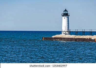 Manistee's tower light on Lake Michigan with some winter ice still on the pier