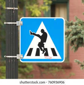Manitou Springs, CO/USA - September 7, 2016 - A crosswalk sign in Manitou Springs, Colorado that references the Ministry of Silly Walks from the popular comedy program Monty Python's Flying Circus.