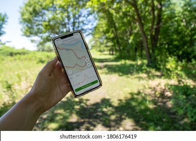 Mankato, Minnesota - June 5, 2020: Hiker uses an AllTrails hiking map app on her phone to navigate the trails in Minneopa State Park