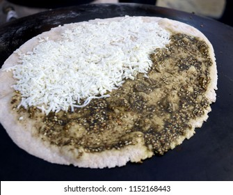 Mankousheh, a Lebanese flatbread made with thyme, oil, spices and cheese seen on a saj oven