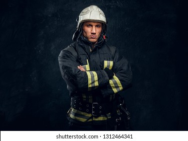 Manly firefighter in helmet looks into camera in studio on black background
