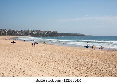 Manly, New South Wales/Australia-December 21,2016: Surfers carrying boards and surfing in the Pacific Ocean waves with oceanfront architecture in Manly, Australia