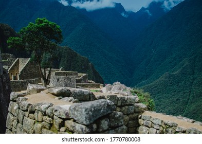 manmade stone structures on a mountain. There are mountains in the background. The sky is cloudy.