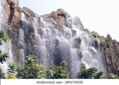 manmade waterfall park. flowing water stream in garden