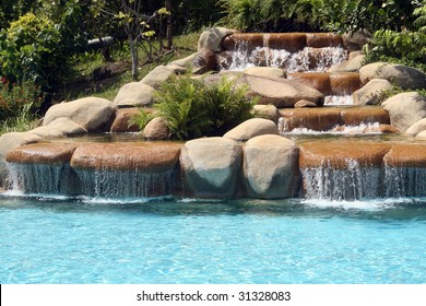 A man-make waterfall at the side of a resort swimming pool.