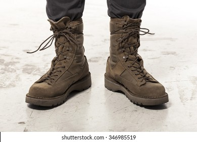 A man(male, boy) wearing khaki(brown) military shoes(combat military boots) and cargo pants at the studio.