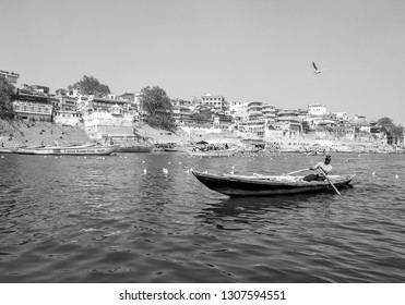 Manmandir ghat,  River Ganges, Varanasi, Uttar Pradesh, India; 30-Jan-2019; a fisherman rowing a boat in the Ganges and some Siberian migratory birds swimming