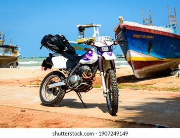 Mannar Island, Sri Lanka - 11th January 2020 : A hired Honda motorcycle is parked next to some fishing boats during a tour of Sri Lanka. An Ortlieb rollbag easily contains all the luggage required.