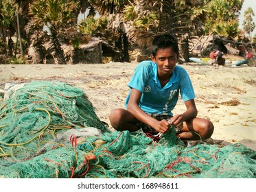 MANNAR/SRI LANKA - FEB 01: Unidentified young Tamil fisherman repairs fish nets on the beach after morning fishing on February 01, 2013 in Talaimannar, Mannar island, Sri Lanka, South Asia.