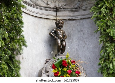 Manneken Pis Of Bruxelles with red flowers
