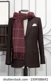 Mannequin with bespoke brown jacket and scarf in atelier. Men's Clothing