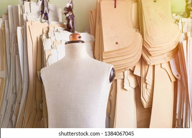 Mannequin in bespoke tailor studio against cardboard sewing patterns.