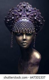 Mannequin in creative purple crown on black background