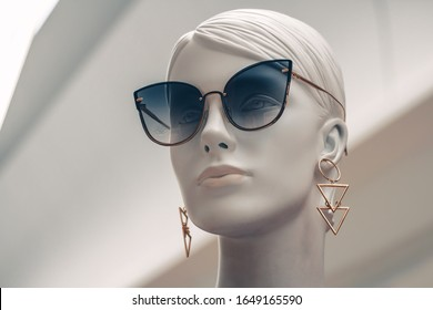 Mannequin face. Portrait of female beautiful dummy in blue sunglasses with earrings on isolated white background. Fashion industry