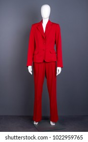Mannequin in female red elegant suit. Full length female mannequin in red blazer and trousers. Feminine elegance and style.