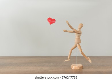Mannequin figure chasing a heart with room for copy.
