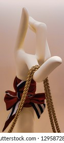 Mannequin finger holdings jewelry necklace. Beige and white colors in background.