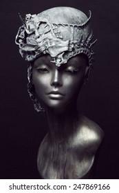 Mannequin in grey stone head wear on black background