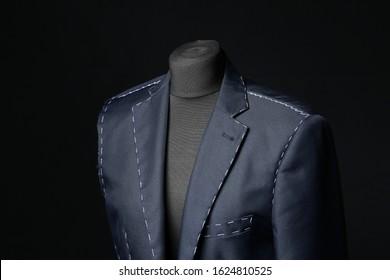 Mannequin with half-finished jacket on dark background