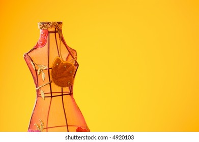 Mannequin made of wire and clothes on warm background.