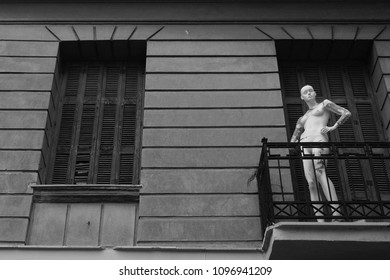 Mannequin on balcony of abandoned house. Black and white.