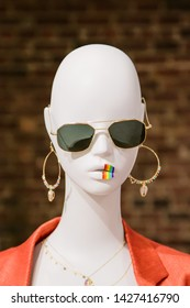 Mannequin with sunglasses and LGBT pride sticker on its lips.