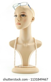 mannequin woman head fake  wearing eyeglasses and pearls necklace without hair isolated on white background