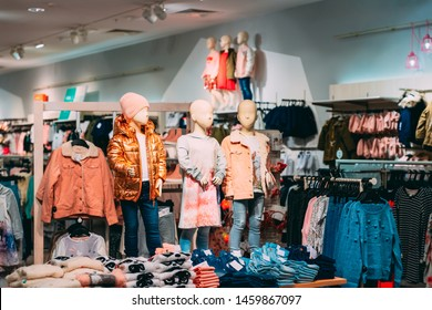 Mannequins Dressed In Children Female Casual Clothes And Colorful Bright Children Clothes On Shelves And Hanger In Store Of Shopping Center.