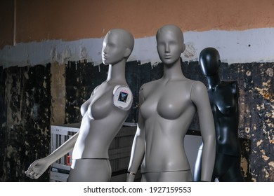 Mannequins standing in an empty warehouse, dark background, white woman as objects, black man in background