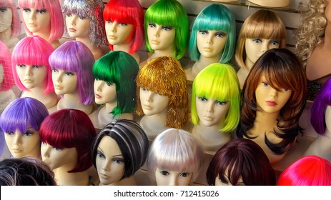 Mannequins wearing colorful wigs in a wig shop store window