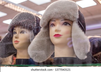 Mannequins in winter hats on the shop window. Selling caps with ear-flaps in the boutique. Russian winter hats. Sale of hats in the store.