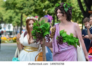 Mannheim, Germany - August 2019: Dionysus and Ariadne cosplayers in full costumes walking by at public park in Mannheim during anual anime and manga