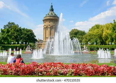 MANNHEIM, GERMANY, AUGUST 22, 2015: Mannheim Water Tower (Mannheimer Wasserturm) a famous landmark with a couple sitting in front of fountain in MANNHEIM
